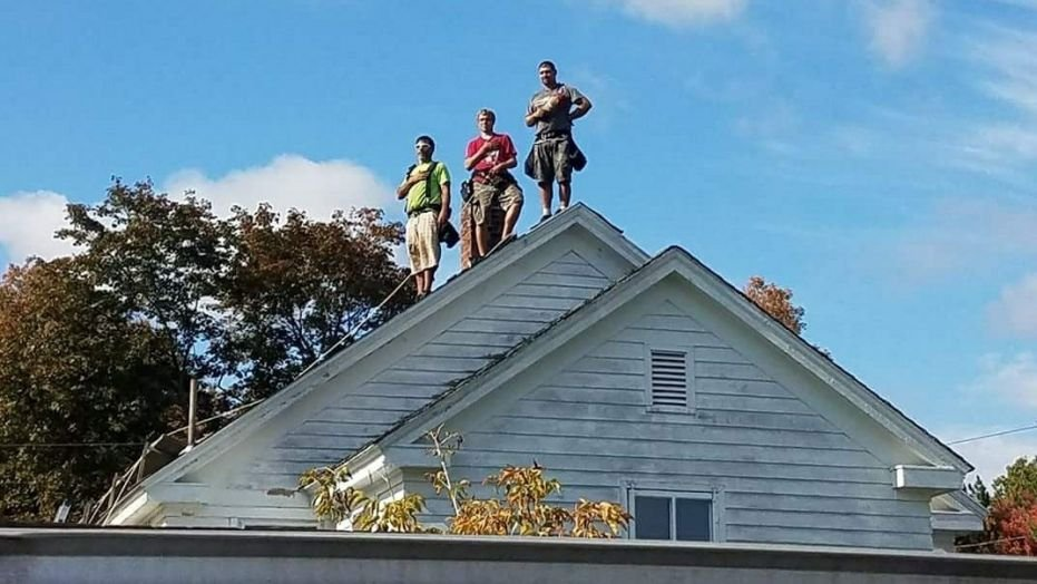 Three roofers put work aside to stand for National Anthem